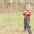 Foto Stock: Little boy holding rifle over his shoulder