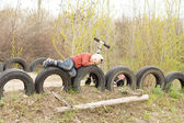 Young boy lying on old tyres — Stock Photo