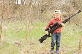 Small boy carrying a rifle — Stock Photo