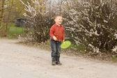 śmiejąc się mały chłopiec bawi się frisbee — Zdjęcie stockowe