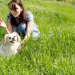 Young woman playing with her dog in grass — Stock Photo