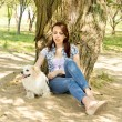 Attractive woman resting in shade with her dog — ストック写真