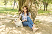 Attractive woman resting in shade with her dog — Stock Photo