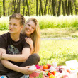 Cute looking boy with pretty girlfriend on picnic - Stock Photo