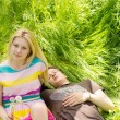 Attractive couple lying down on the grass — Stock Photo
