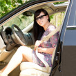 Young attractive brunette woman in a car — Stock Photo