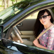 Close up of an attractive brunette woman in a car — Stock Photo