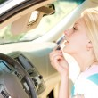 Royalty-Free Stock Photo: Woman applying makeup in a car