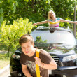 Handsome young man towing a car — Stock Photo