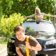 Handsome young man towing a car - Stock Photo