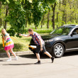 Lazy man watching his girlfriend pull a car — Stock Photo