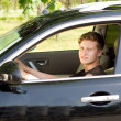 Smiling young man driving a car — Stockfoto