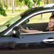 Cute young boy driving a black car and posing — Stock Photo