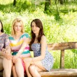 Three attractive girls on a wooden bench — Stock Photo