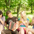 Friends enjoying music played on a concertina — Stock Photo