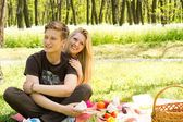 Cute looking boy with pretty girlfriend on picnic — Stock Photo