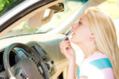 Woman applying makeup in a car — Stock Photo