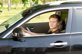Smiling young man driving a car — Stock Photo