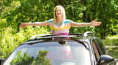 Playful woman standing in a car sunroof — Stock Photo