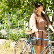 Woman with her bike outside a country home — Stock Photo
