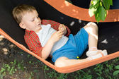 Cute kid lying and playing on the swing — Stock Photo