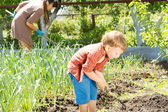 Little boy working with his mother in the garden — Stock Photo