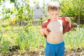 Hot little boy removing his shirt — Stock Photo