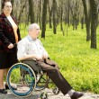 Woman walking her husband in his wheelchair — Stock Photo