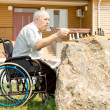 Disabled man playing chess in his garden — Stock Photo