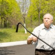 Stock Photo: Elderly mwaving his crutch in air