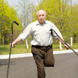 Stock Photo: Elderly disabled mbalancing on one leg