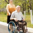 Wife taking her disabled husband for a walk — Stock Photo #25461097