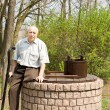 One legged man sitting on an old well — Foto Stock