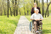 Wife walking a disabled man in a wheelchair — Stock Photo