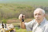 Elderly man holding up a chess piece — Stock Photo