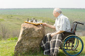 Handicapped pensioner playing chess outdoors — Stock Photo