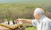 Retired man playing chess in the countryside — Stock Photo