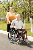 Wife taking her disabled husband for a walk — Stock Photo