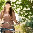 Smiling woman with her bicycle — Stock Photo