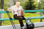 Handicapped senior man with an accordion — Stock Photo