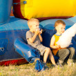 Two young boys eating cotton-candy near a slide — Stock Photo #26144365