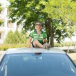 Young boy sitting on the top of a car looking up — Stock Photo #26144411