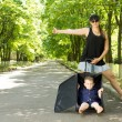 Woman hitchhiking with her son — Stock Photo