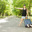 Mother hitchhiking with her son in a suitcase — Stock Photo