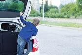 Kind permanent in de open kofferbak van een auto — Stockfoto