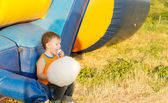 Young boy eating cotton-candy sitting near a slide — Stock Photo