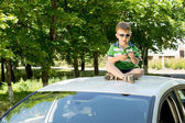 Young boy sitting on the top of a car playing — Stock Photo