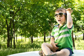 Young boy sitting on the top of a car with a phone — Stock Photo
