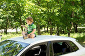 Young blond boy sitting on the rooftop of a car — Stock Photo