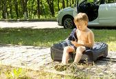 Giovane ragazzo seduto su una borsa da viaggio sul ciglio della strada — Foto Stock